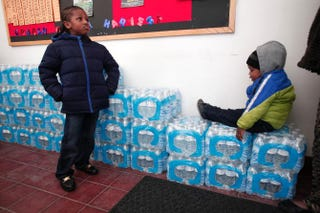 Justin Roberson, age 6, and Mychal Adams, 1, wait on a stack of bottled water at a rally where the Rev. Jesse Jackson was speaking about the water crisis at the Heavenly Host Baptist Church in Flint, Mich., Jan. 17, 2016.Bill Pugliano/Getty Images