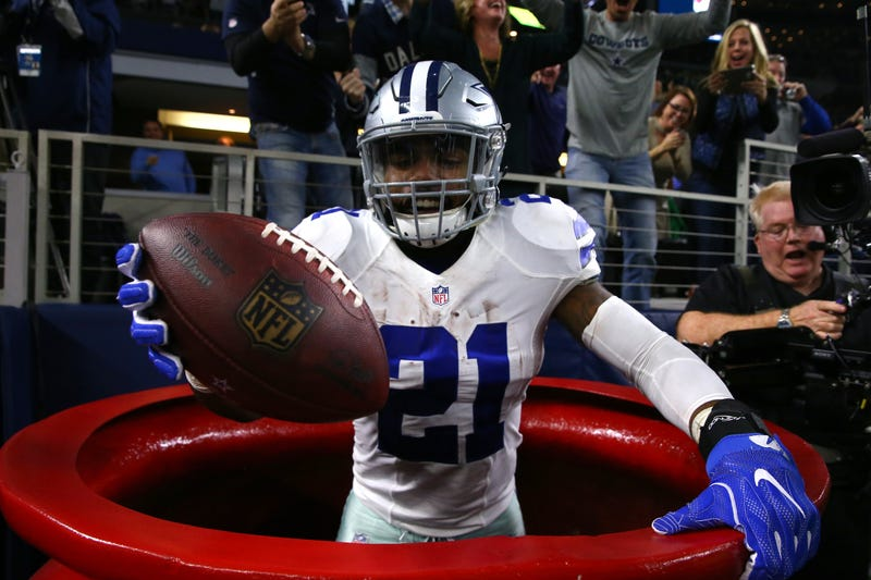 Ezekiel Elliott, No. 21 of the Dallas Cowboys, celebrates Dec. 18, 2016, after scoring a touchdown by jumping into a large Salvation Army red kettle during the second quarter of a game against the Tampa Bay Buccaneers in Arlington, Texas.Tom Pennington/Getty Images