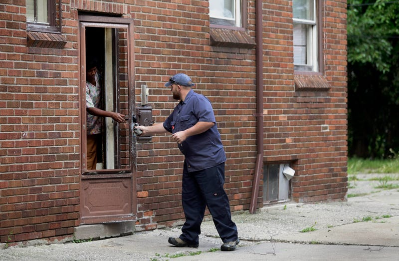 A worker from Homrich talks to a resident on Aug. 27, 2014, in Detroit after turning their water back on. It was disconnected by the Detroit Water and Sewerage Department, which disconnected water to thousands of Detroit residents with delinquent bills.