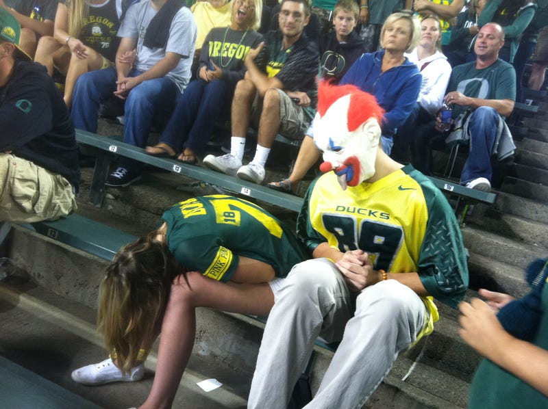 Illustration for article titled There's A Lot Going On In This Photo Of A Passed-Out Oregon Ducks Fan Being Ogled By A Creepy Clown