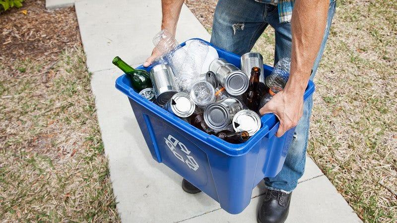 Man holding a recycling bin.