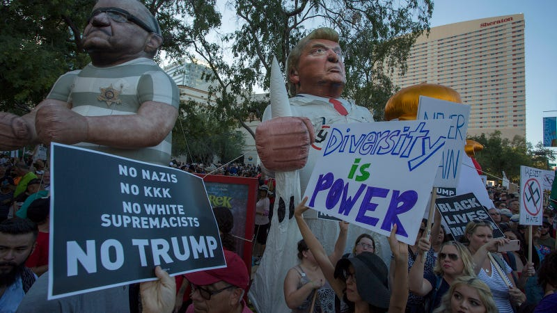Large inflated figures of Sheriff Joe Arpaio (L) and President Trump are seen above ant-Trump protesters outside the Phoenix Convention Center at a rally by President Donald Trump on August 22, 2017 in Phoenix, Arizona