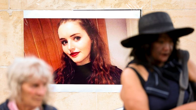 Members of the public walk past a photo of Grace Millane during a vigil at Civic Square on December 12, 2018 in Wellington, New Zealand.
