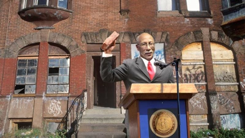 Mayor David Bing christens the brand-new housing development by shattering the window of a dilapidated tenement building.