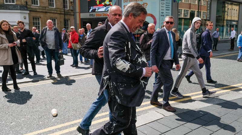 Brexit Party leader Nigel Farage has what is reported to be a milkshake thrown on him as he visits Northumberland Street in Newcastle Upon Tyne, England, on May 20.