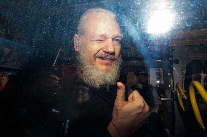 Julian Assange gestures to the media from a police vehicle on his arrival at Westminster Magistrates court on April 11, 2019 in London, England.