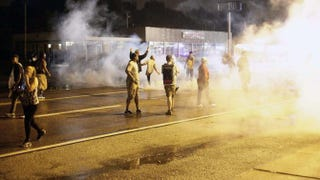 Demonstrators protesting the Aug. 9 fatal police shooting of 18-year-old Michael Brown react as police fire tear gas on the streets of Ferguson, Mo., on Aug. 17, 2014. A crowd of some 200 demonstrators defied a curfew that went into effect in Ferguson early on Aug. 17, days after police shot dead the unarmed black teen, triggering a wave of protest.Joshua LOTT/AFP/Getty Images