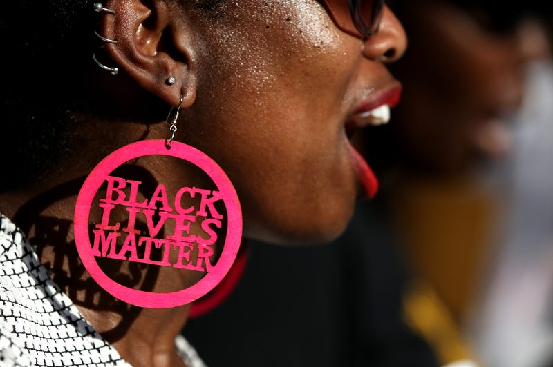 A Black Lives Matter protester wears custom earrings during a demonstration outside of office of Sacramento district attorney Anne Schubert on March 28, 2018 in Sacramento, California.