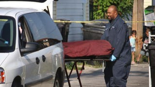 The body of a man is removed from a yard in the Kelvyn Park neighborhood of Chicago July 28, 2008.Scott Olson/Getty Images