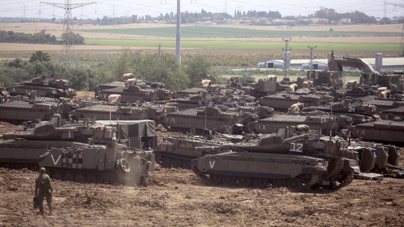 Israeli soldiers walks in front of a Merkava tanks, stationed near the border with the Gaza Strip on May 6, 2019 in Mavkim, Israel.