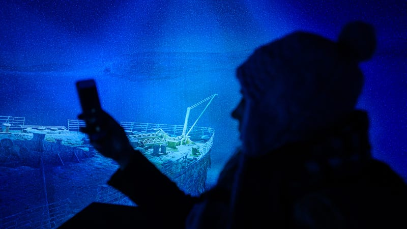 A woman takes a picture at a replica of the shipwreck