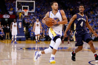 Stephen Curry of the Golden State Warriors drives to the hoop against Ish Smith of the New Orleans Pelicans during the NBA season opener in Oakland, Calif., Oct. 27, 2015.Ezra Shaw/Getty Images