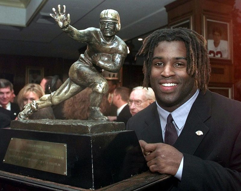 Ricky Williams, winner of the 1998 Heisman Trophy, poses with U.S. college football's highest honor at the Downtown Athletic Club in New York City.ADAM NADEL/AFP/Getty Images