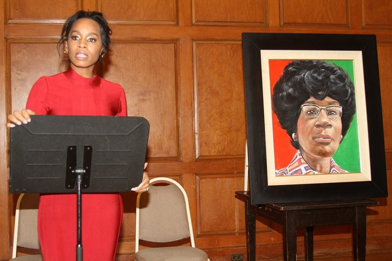 Anika Noni Rose stands near a portrait of Shirley Chisholm.Facebook