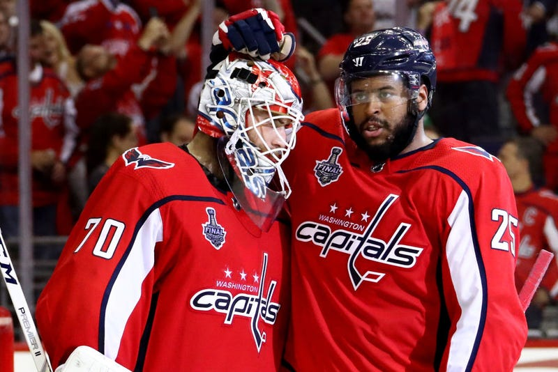 Braden Holtby, No. 70, and Devante Smith-Pelly, No. 25, of the Washington Capitals celebrate their team's 6-2 win over the Vegas Golden Knights in Game 4 of the 2018 NHL Stanley Cup Final at Capital One Arena on June 4, 2018, in Washington, D.C.