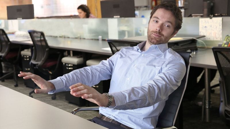 Man On Rolling Swivel Chair Pushes Away From Desk Like