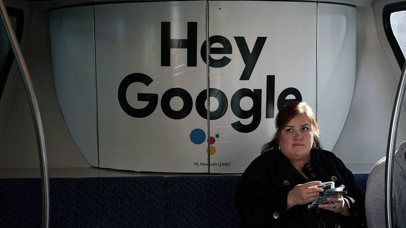 A woman sits in a Las Vegas Monorail car with a Google ad prior to the CES 2018.