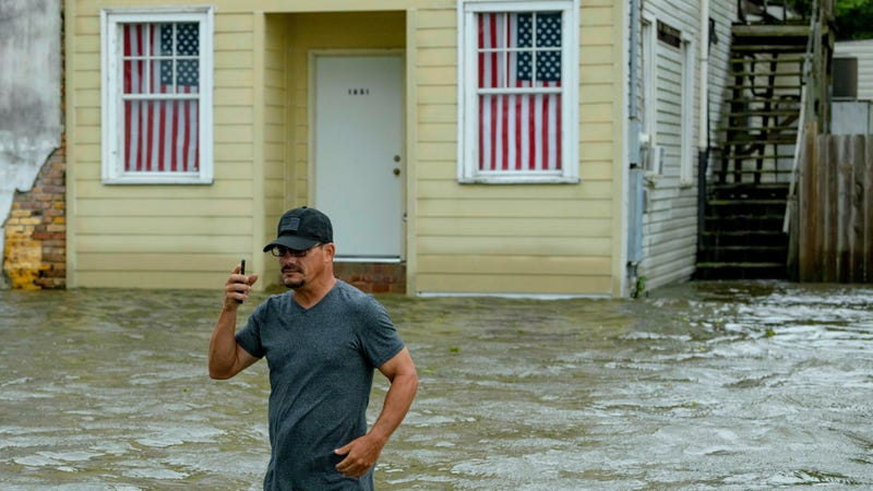 Barry Williams wading through storm surge from Lake Ponchartrain on July 13 in Mandeville, Louisiana.