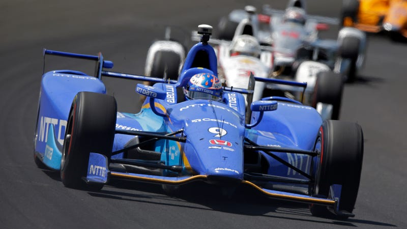 Indianapolis 500 pole sitter Scott Dixon leads a pack of cars during practice. Photo credit: AP Photo/Michael Conroy