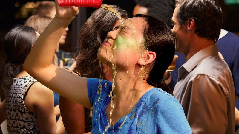 A woman pouring a drink on her face.