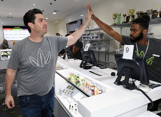 Essence Vegas CEO Armen Yemenidjian (left) high-fives employees at Essence Vegas Cannabis Dispensary as they get ready for the midnight start of recreational marijuana sales on June 30, 2017, in Las Vegas. (Ethan Miller/Getty Images)