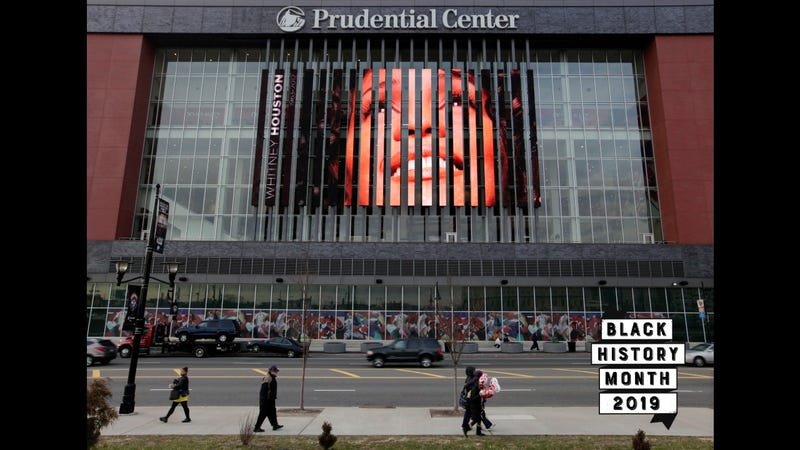 People walk past a large image of Whitney Houston displayed on the side of the Prudential Center in Newark, N.J., Feb. 14, 2012. Officials had discussed the possibility of holding a memorial at the Prudential Center, a major sports and entertainment venue that can seat about 18,000 people, but instead Houston's homegoing was held at her home church, New Hope Baptist, in Newark. (AP Images)