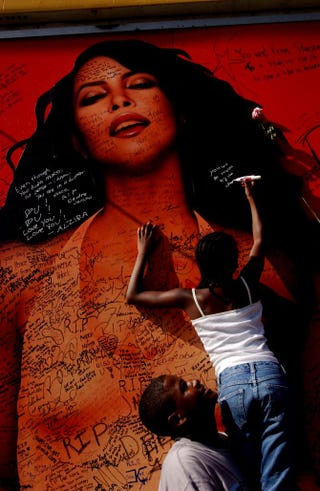 Ten-year-old Ravyn Charles (top), with her brother, 15-year-old Joshua, writes a message on a billboard for the late singer and actress Aaliyah Aug. 28, 2001, on Sunset Boulevard in Hollywood, Calif.David McNew/Getty Images