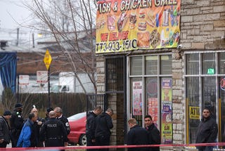 Chicago police officers investigate the scene where four people were shot and killed at a restaurant in the 2700 block of East 75th Street on March 30, 2017. (Joshua Lott/Getty Images)