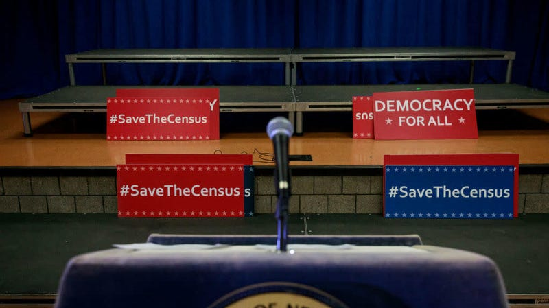 Signs sit behind the podium before the start of a press conference April 3, 2018, with the then New York attorney general Eric to announce a multistate lawsuit to block the Trump administration from adding a question about citizenship to the 2020 census form.