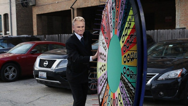 Pat Sajak wheeling the Wheel Of Fortune wheel out to his car.