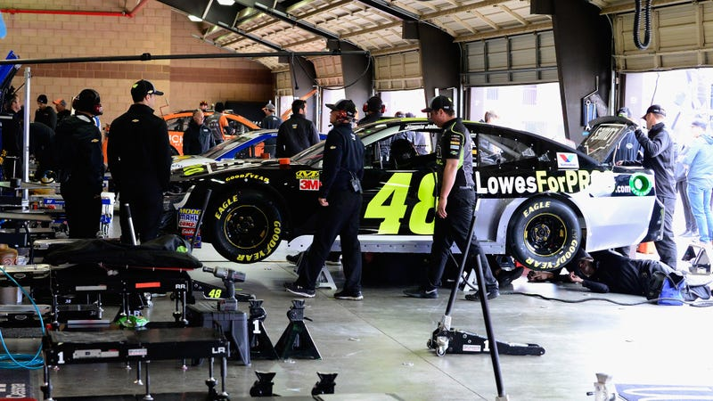 Jimmie Johnson's team works on the car after failing inspection before the race at Auto Club Speedway in 2018.