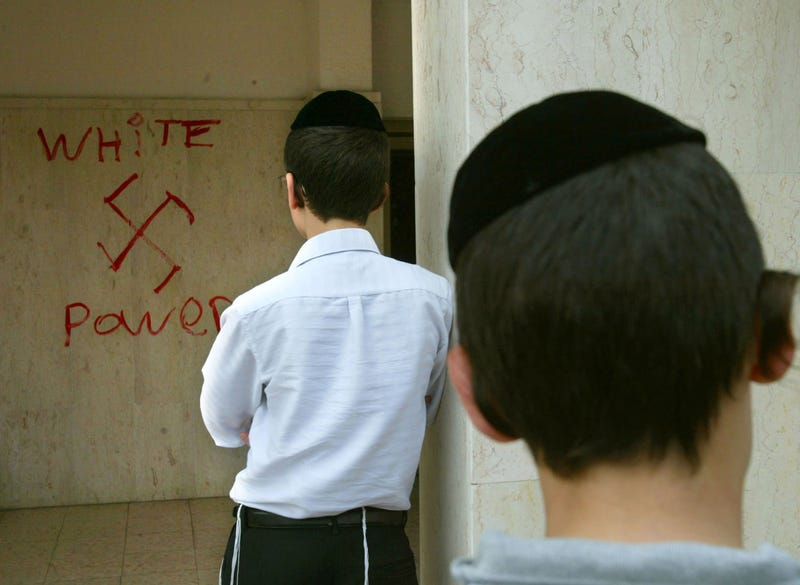 Jewish boys look at anti-Semitic graffiti which was sprayed on the walls of a synagogue March 5, 2006