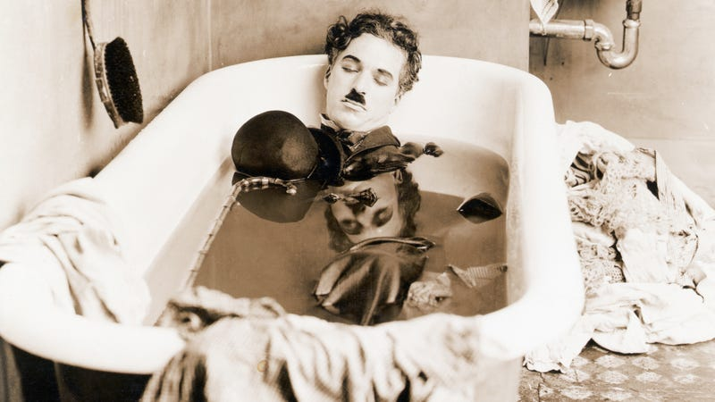 Charlie Chaplin sleeps in a bathtub in a scene from his 1922 film, Pay Day.