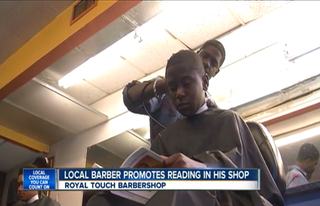 Royal Touch Barbershop owner Reggie Ross gives a haircut to a young customer while he reads.WPTV Screenshot