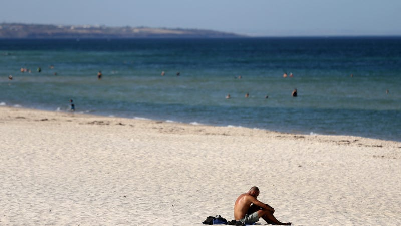 A man sits on a beach in Adelaide, Australia, on January 24, when temperatures soared north of 115 degrees Fahrenheit.
