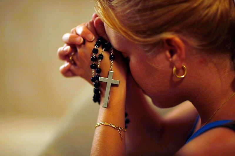 Susy Vazquez prays before a shadow that has formed what many think is the silhouette of Joseph and the Virgin Mary standing over the baby Jesus at St. Brendan Catholic Church's Adoration Chapel on Sept. 21, 2007, in Miami. (Joe Raedle/Getty Images)