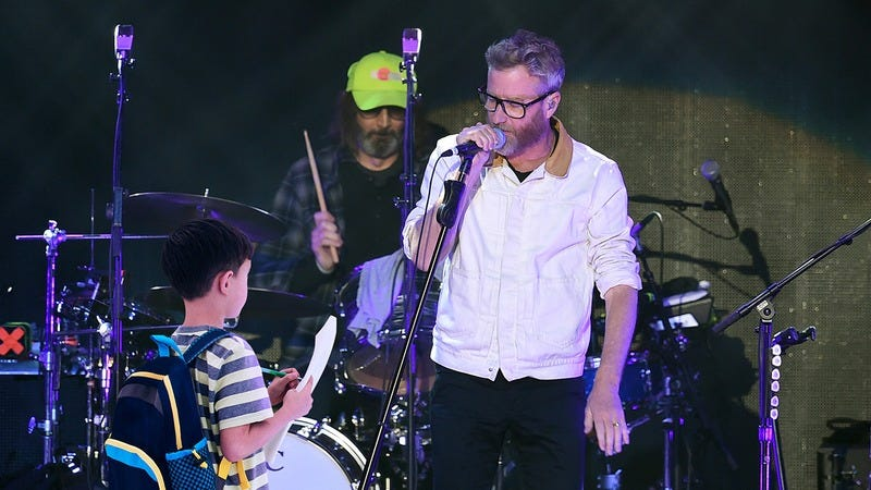 The National singer talking to a child on stage.