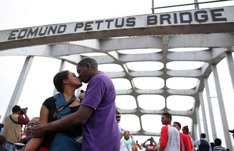 A couple stops to kiss as they join thousands of people walking across the Edmund Pettus Bridge during the 50th anniversary commemoration of the Selma-to-Montgomery civil rights march on March 8, 2015, in Selma, Ala. Justin Sullivan/Getty Images