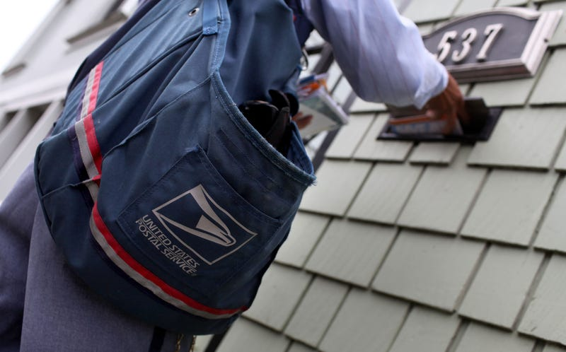 U.S. Postal Service letter carrier Anthony Ow places letters in a mailbox as he walks his delivery route July 30, 2009, in San Francisco. (Justin Sullivan/Getty Images)
