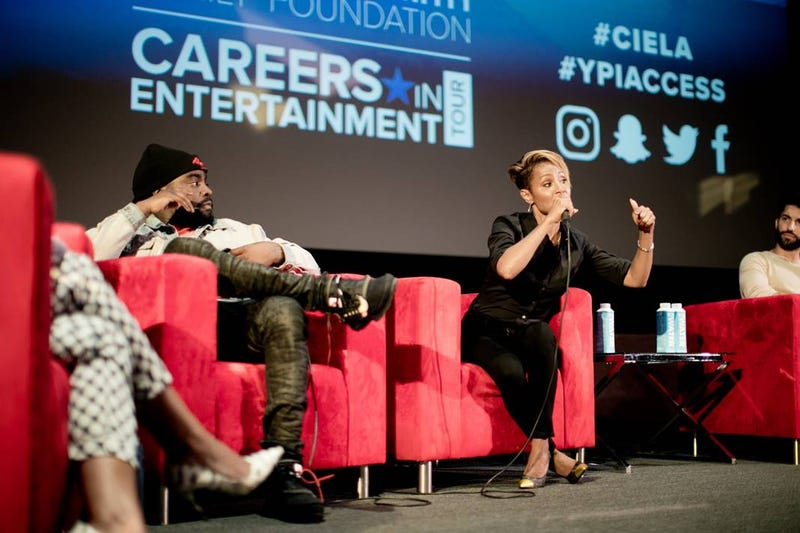 Warner Bros. recording artist Wale looks on while Jada Pinkett Smith talks about her path as an actress and content creator at the Careers in Entertainment summit on July 28, 2018, at UCLA.