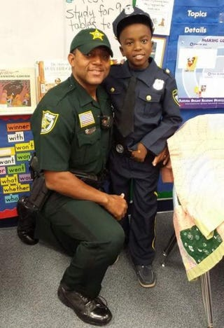 Palm Beach County Sheriff's Deputy Fernandas Jones poses with an unidentified child dressed as an officer.Palm Beach County Sheriff's Office viai Twitter