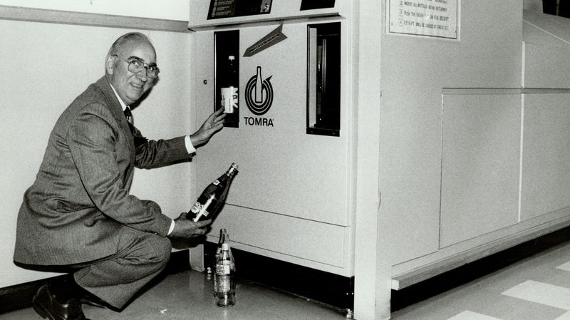 A man demonstrates an early-model Tomra reverse vending machine in Canada.