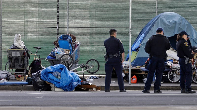 San Francisco police officers wait while homeless people collect their belongings Tuesday, March 1, 2016, in San Francisco.