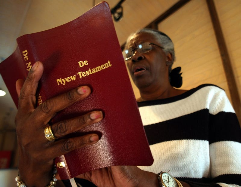 "Ervena Faulkner, the co-manager of history and culture at the Penn Center, holds a copy of ""De Nyew Testament,"" Nov. 9, 2005, in St. Helena Island, S.C. The New Testament has been translated into Gullah, the creole language spoken by slaves and their descendants for generations along the Sea Islands of the Southeast coast. (Stephen Morton/AP Images)"