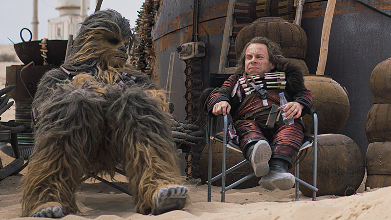 Chewbacca (Joonas Suotamo) and Weazel (Warwick Davis) take a brief moment of relaxation on Savareen.