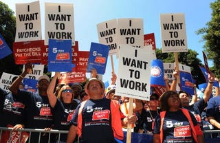 "Americans hold up ""I Want to Work"" signs. (Getty)"