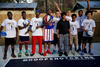 Harlem Globetrotter Buckets Blakes poses for a photo with the original #HoopsNotCrime kids from the Gainesville, Fla., community.Gainesville, Fla., Police Department