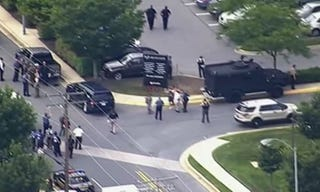 Law enforcement officials are seen outside the Capital Gazette offices in Annapolis, Md., after authorities say a gunman opened fire and killed at least five people.