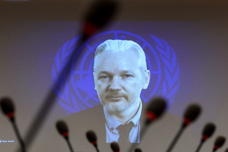 WikiLeaks founder Julian Assange is seen on a screen speaking via webcast from the Ecuadorian Embassy in London during a United Nations refugees agency event March 23, 2015, in Geneva.FABRICE COFFRINI/AFP/Getty Images