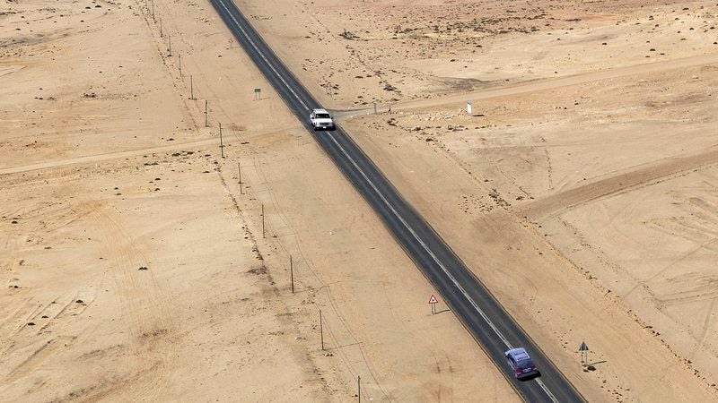 Two cars driving at each other in the desert.